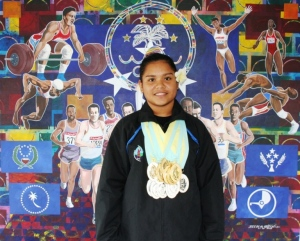 FSM Swimmer Debra Daniel poses with FSMNOC mural painting with medals: 7 Gold, 6 Silver!